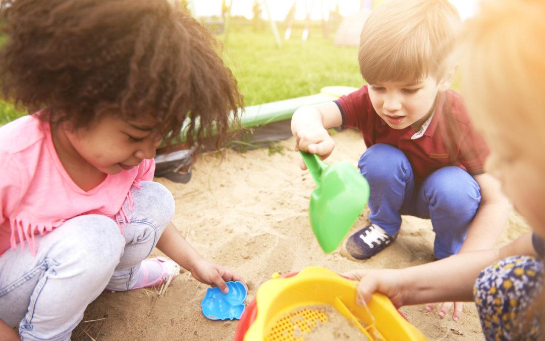 Three diverse children are playing in a sandbox.
